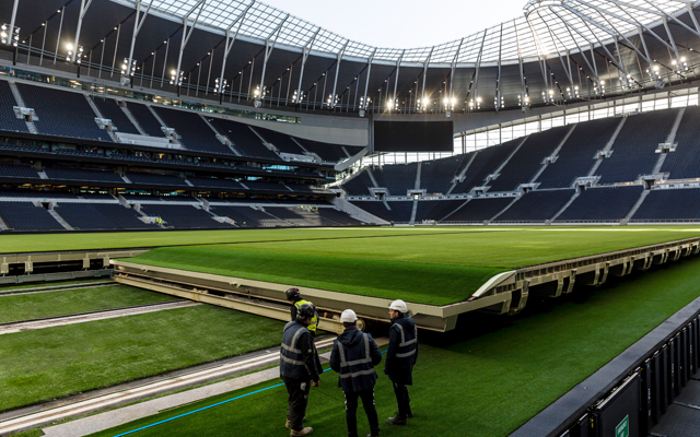 The SCX Special Projects team inspect the retractable pitch during installation at Tottenham Hotspur's new stadium