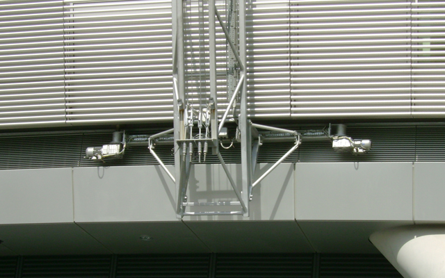 Bespoke building maintenance unit (BMU) on rails set into the building at the top and bottom of the aluminium facia