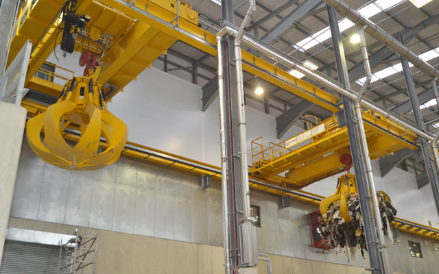 Energy from Waste (EfW) Crane with two orange peel grabs, one in use and one not